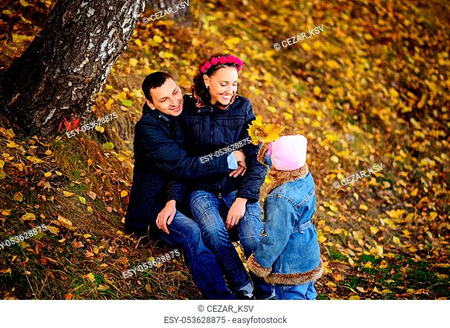 Parents look at children in autumn park, A lovely sunny day