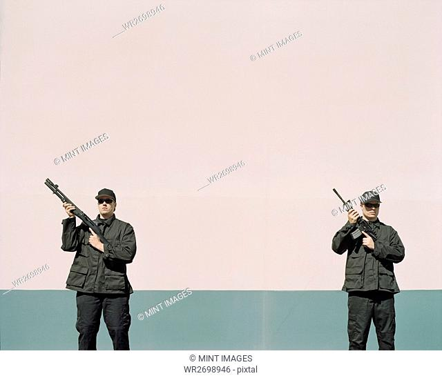 Two men wearing special forces uniforms, holding high powered guns