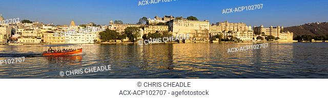 Panoramic image of City Palace with tour boat on Lake Pichola, Udaipur, Rajastan, India