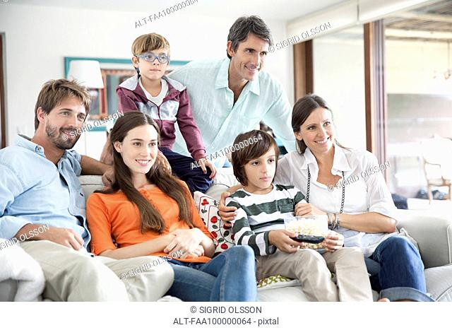 Extended family watching TV together