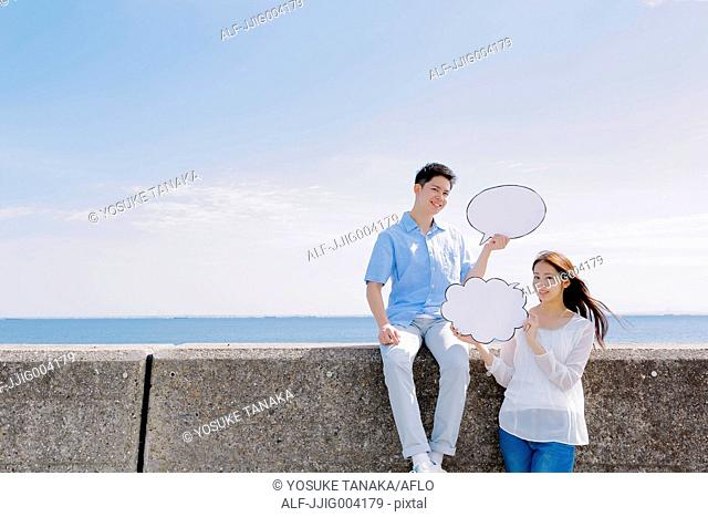 Young Japanese couple with message boards by the sea