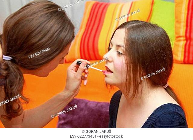 A stylist putting on lip gloss on a girl's face