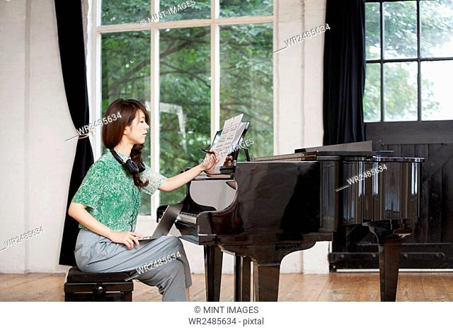 Young woman sitting at a grand piano in a rehearsal studio, annotating sheet music