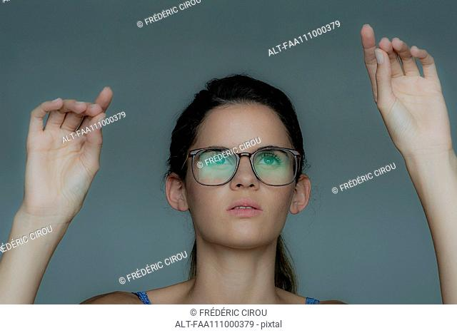 Young woman gesturing as if using touch screen technology