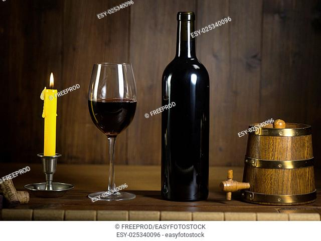 Pouring red wine into wineglass from green bottle, brown background