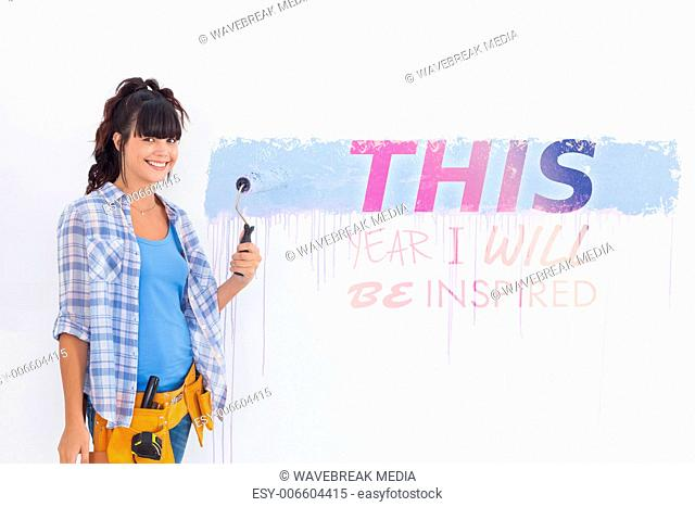 Composite image of woman painting wall blue and smiling