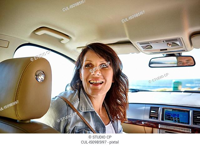 Woman in passenger side of car, looking behind at back seat