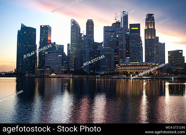Singapore, Republic of Singapore, Asia - General view across Marina Bay of the illuminated central business district with its modern skyscrapers at dusk amid...