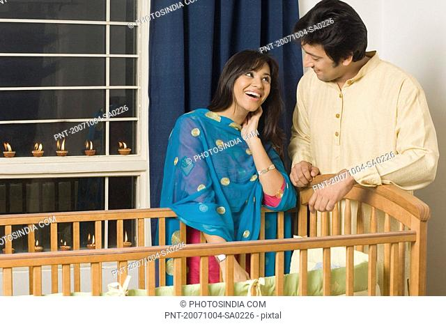 Young woman and a mid adult man standing near a crib and smiling