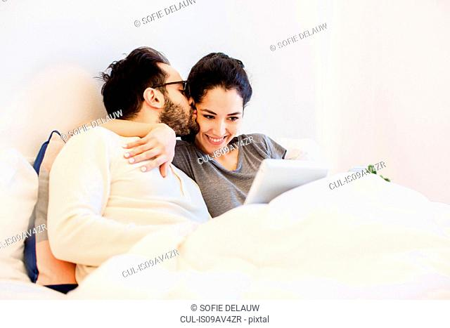Romantic young couple sitting up in bed using digital tablet