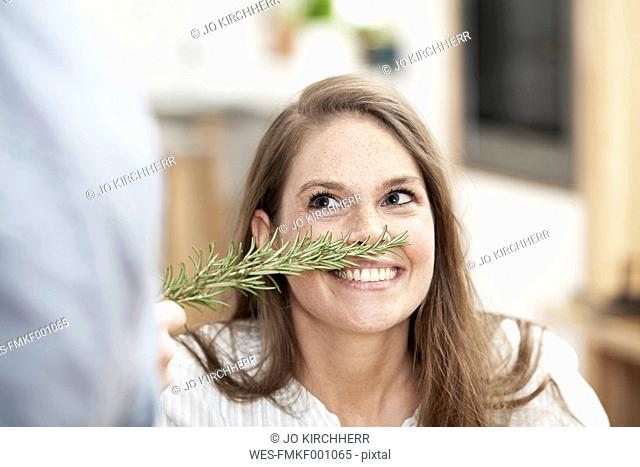 Woman smelling at twig of rosemary