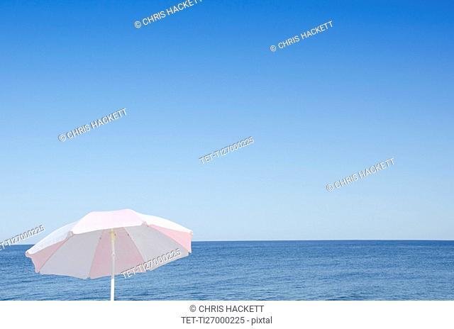Sunshade against blue seascape