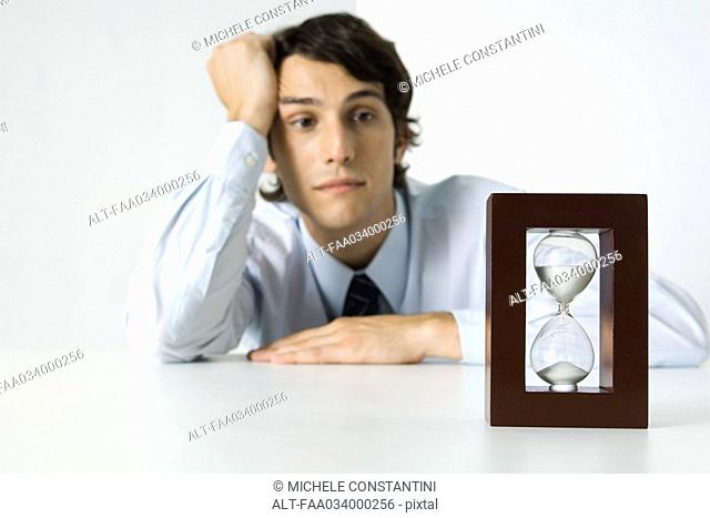 Young man looking at hourglass, holding head