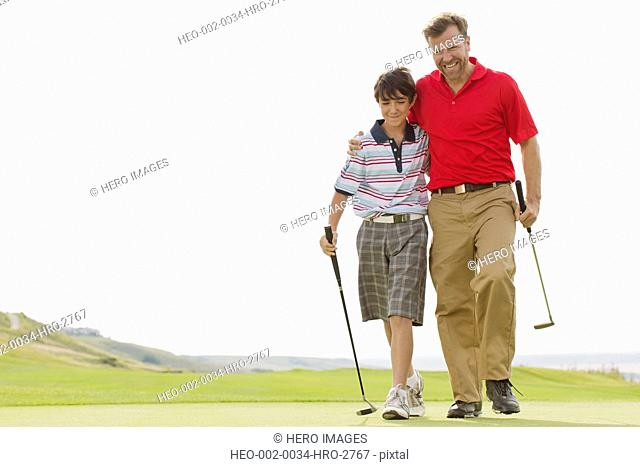 father and son walking on golf green together