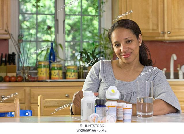 Hispanic woman at a dining table with pill bottles