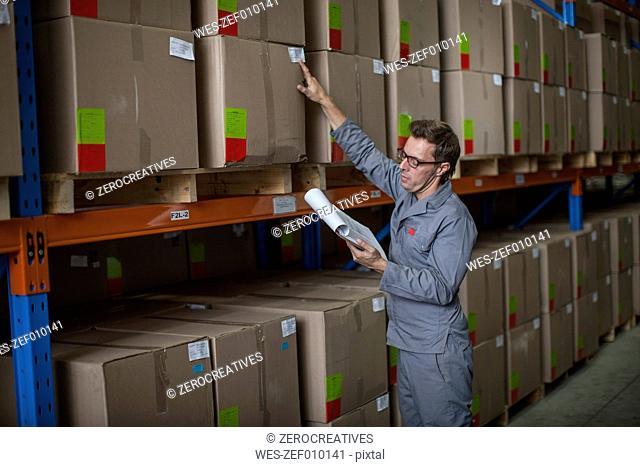 Worker taking stock in warehouse
