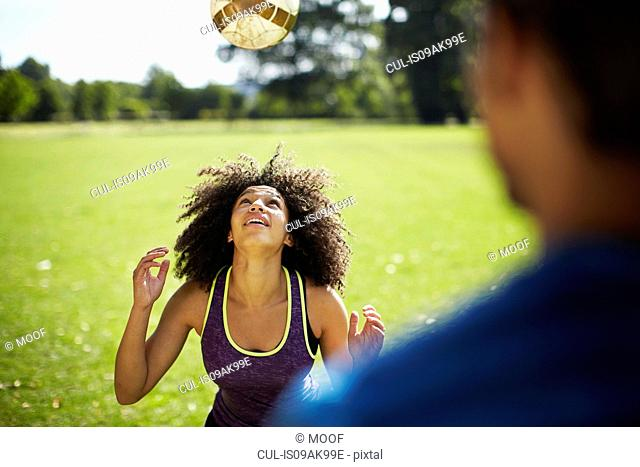 Young woman heading football in park