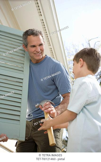 Father and young son fixing shutters