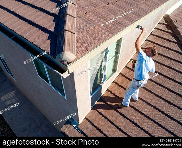 Professional Painter Using A Brush to Paint House Fascia
