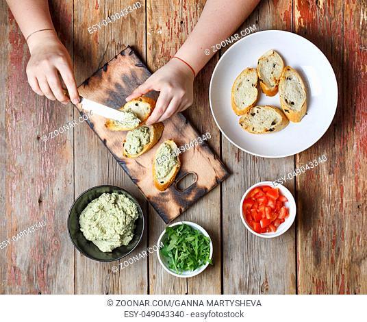 Preparation of bruschetta. Closeup view from above, female hands prepare traditional Italian bruschettes. top view