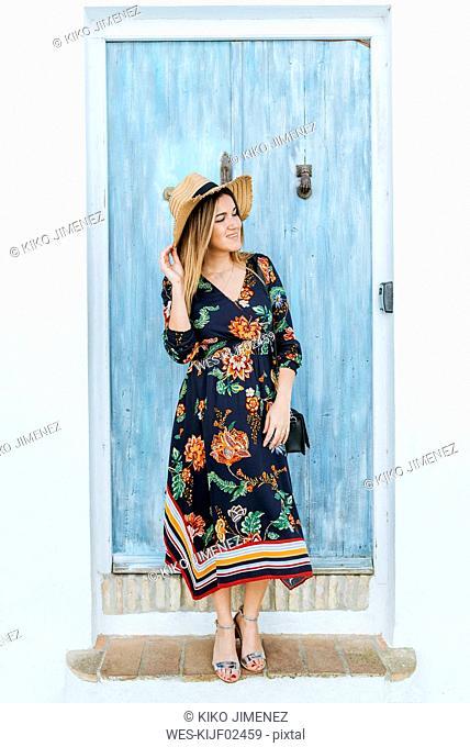 Spain, Cadiz, Vejer de la Frontera, fashionable woman standing in front of light blue wooden door