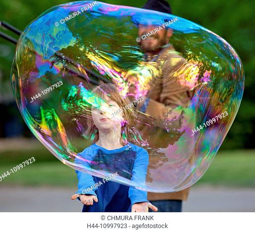 Boy Catching Large Soap Bubble Outdoors
