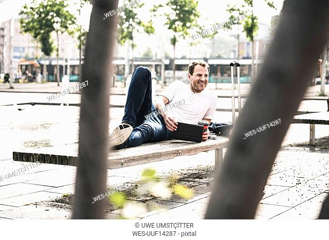 Smiling man lying on bench with tablet