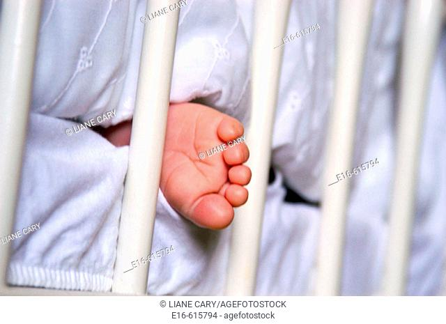 infant foot sticking out of crib