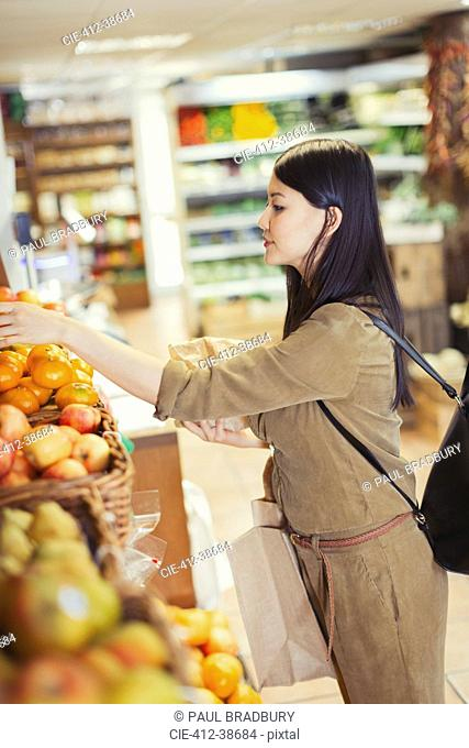 Young woman shopping for produce in grocery store