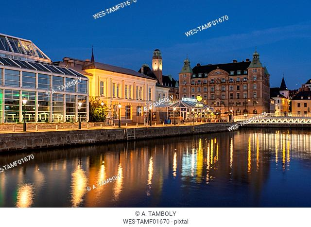 Illuminated buildings by canal at night in Malmo, Sweden