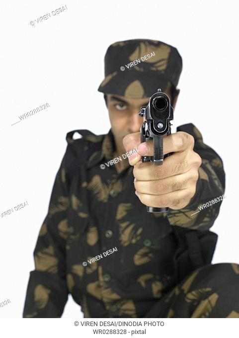 Indian army soldier sitting and pointing handgun MR702A