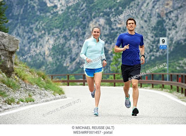 Italy, Trentino, couple running on road near Lake Garda