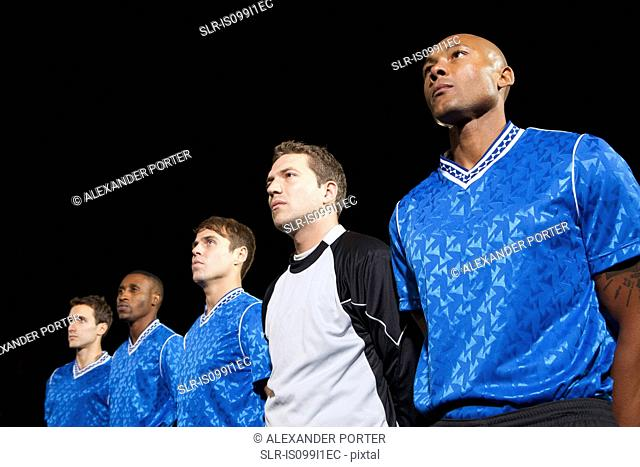 Soccer players standing in line on pitch at night
