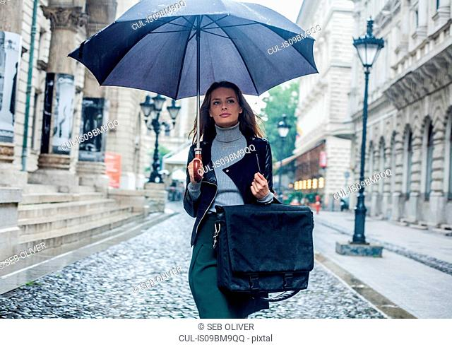 Woman with umbrella on morning commute, Budapest, Hungary