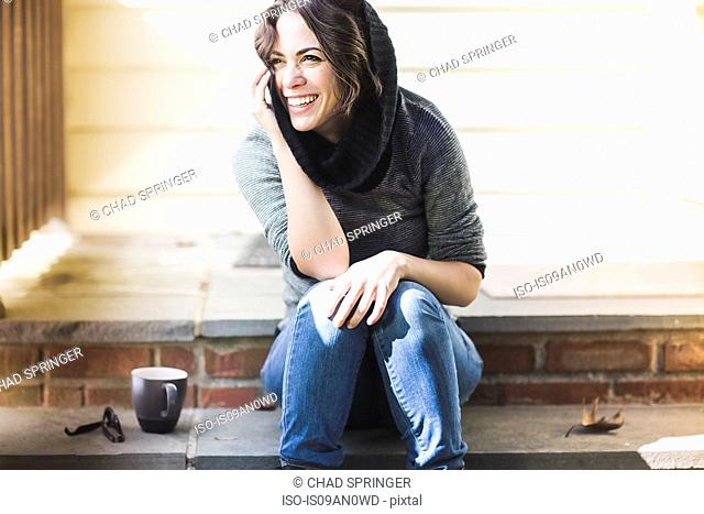 Smiling young woman sitting on porch step