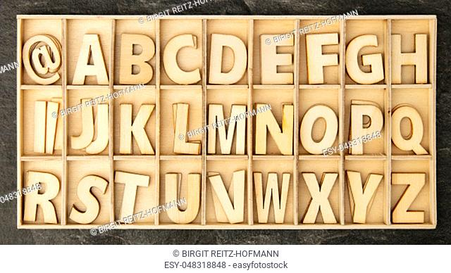 Wooden toy letters in a Box on dark background