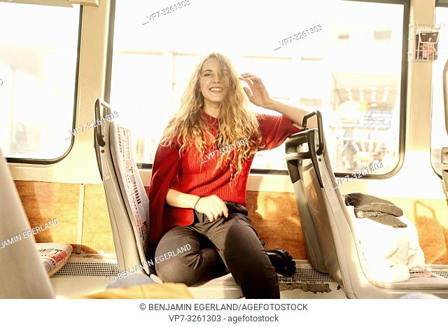 young authentic happy woman with ruffled hair in public transportation, in city Cottbus, Brandenburg, Germany