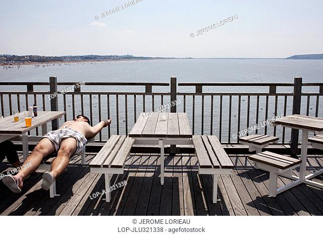 England, Somerset, Weston Super Mare. Man relaxing and view over the Severn Estuary