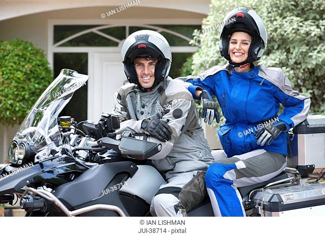 Portrait of smiling couple wearing helmets on motorcycle in driveway