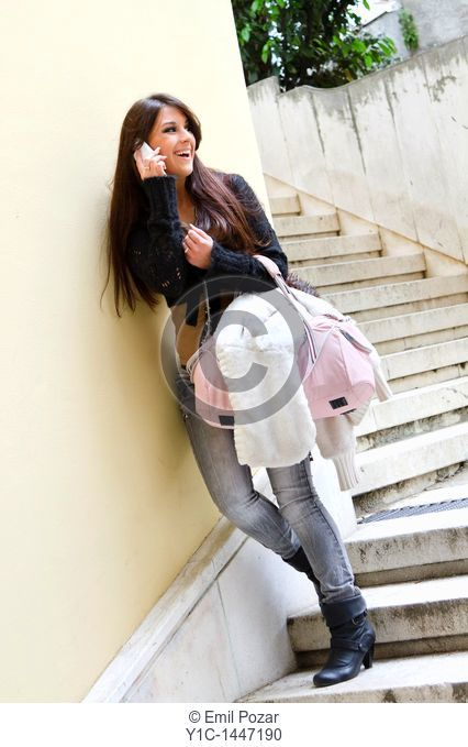 Attractive young woman is talking on a cellular phone on a staircase, smiling