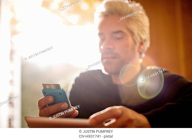 Man with credit card using digital tablet and smart phone