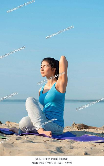 Woman practicing yoga against a sea background