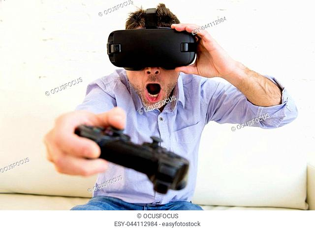 young modern man at home living room sofa couch playing video game excited using 3d goggles watching 360 virtual reality vision enjoying the fun cyber...