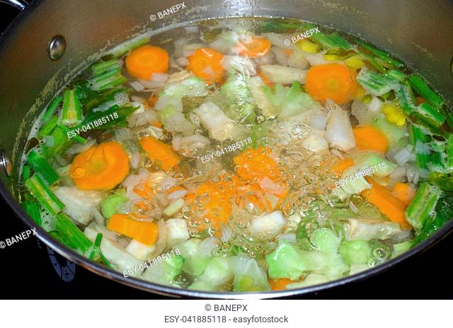 Pot with boiling water with fresh cut vegetables