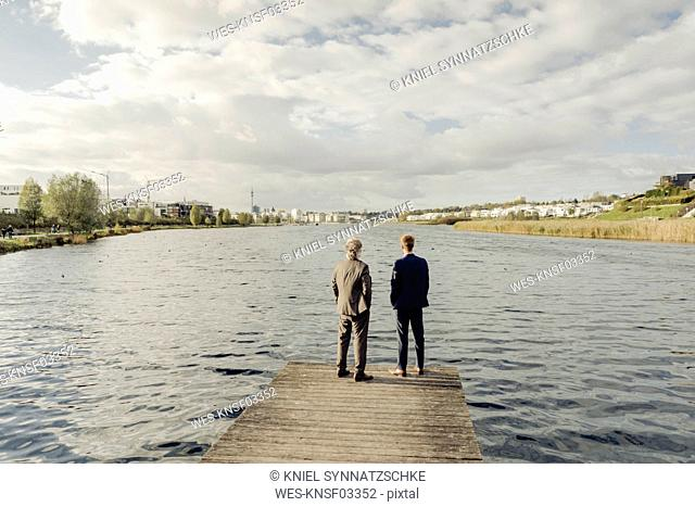 Two businessmen standing on jetty at a lake