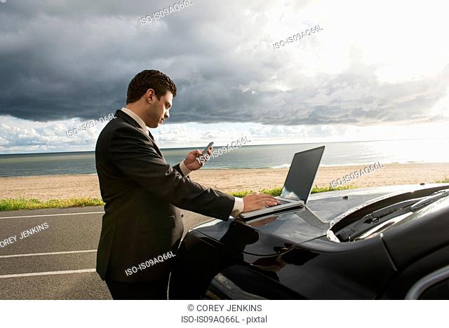 Businessman texting on smartphone whilst using laptop at coastal parking lot