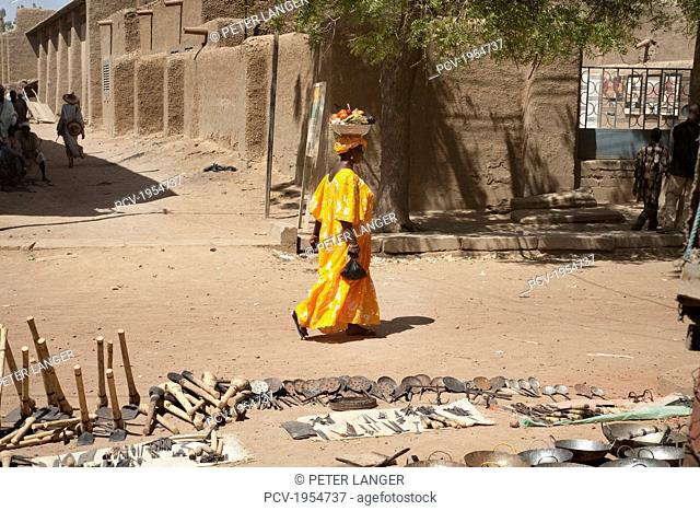 Farming implements for sale with woman walking in the background at the Monday Market in Djenne, Mali
