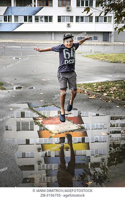 Boy jumps a street puddle