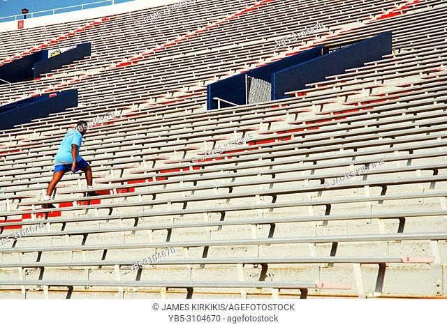 A young athlete uses the steps of the Vaught Hemmingway Stadium at the University of Mississippi as part of his exercise routine