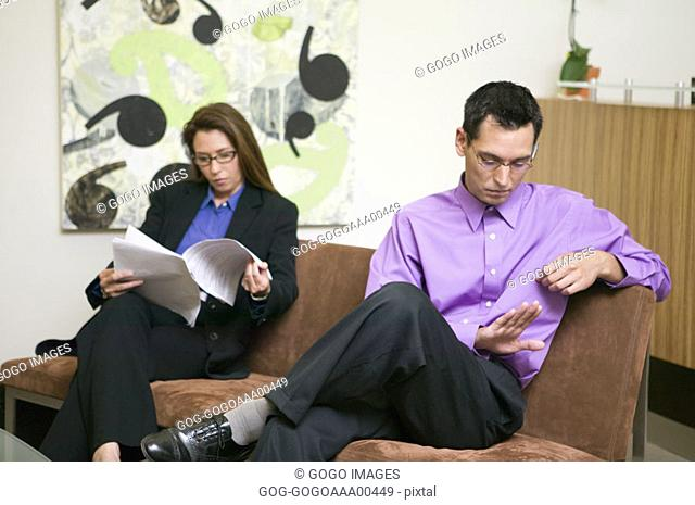 Businessman and businesswoman sitting on sofa in waiting area